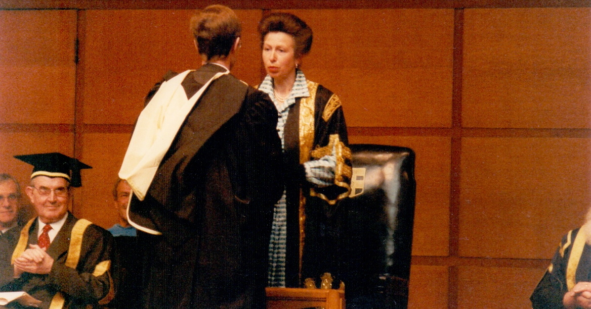 Man in graduation robes being congratulated.
