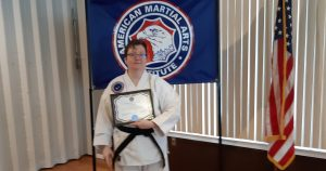 The author wearing her black-belted gi holding her certificate.