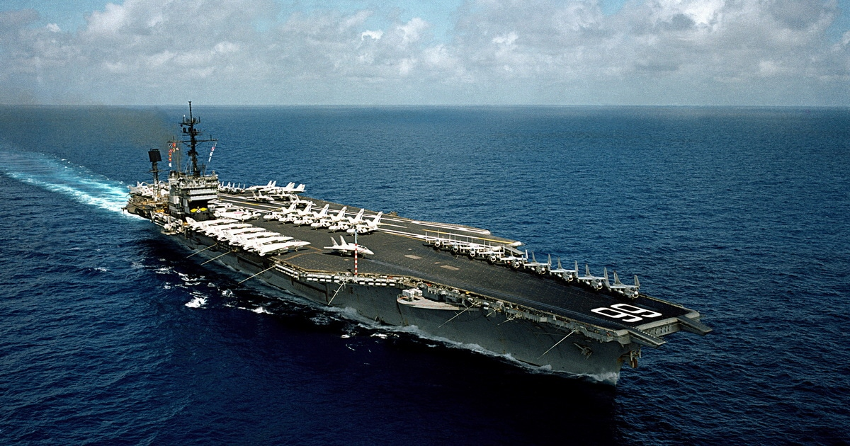 Aircraft carrier underway on a beautiful blue sea.